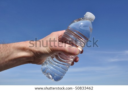Hand Offering a Bottle of Water Against a Blue Sky