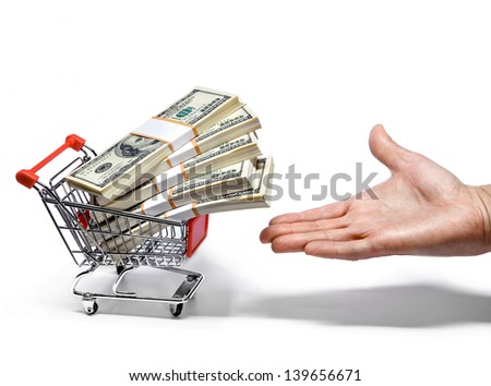 Hand offers shopping cart full of money stacks - stock photo