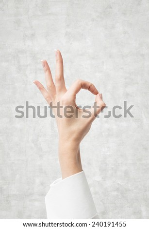 Hand OK sign on a gray background - stock photo