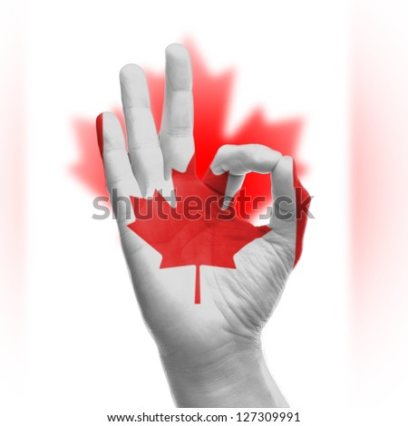hand OK sign, wrapped in the flag of Canada - stock photo