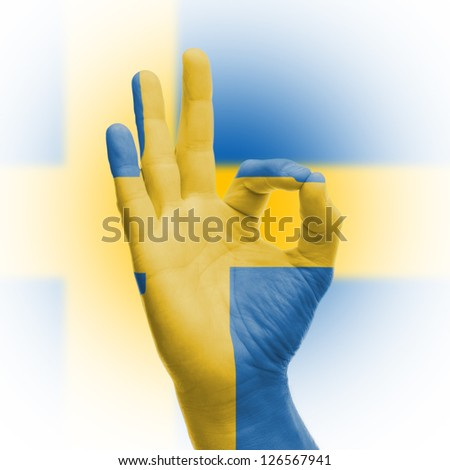 hand OK sign, wrapped in the flag of Sweden - stock photo
