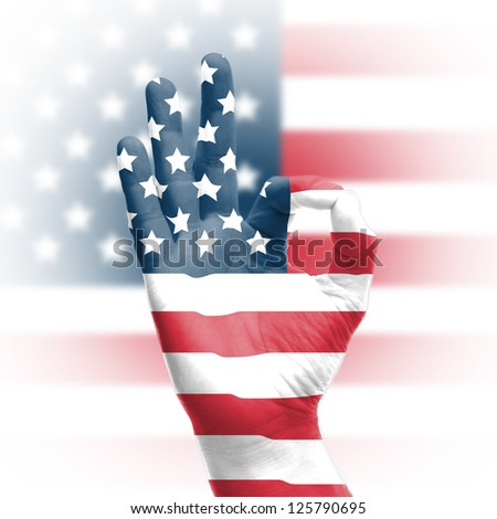 hand OK sign, wrapped in the flag of the USA - stock photo