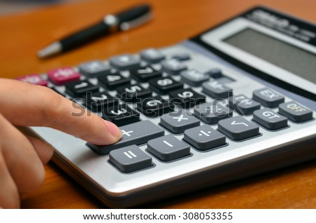 Hand on a calculator (Calculating, business, office objects) - Selective focus - stock photo