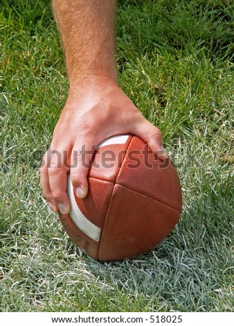 hand on a football - stock photo