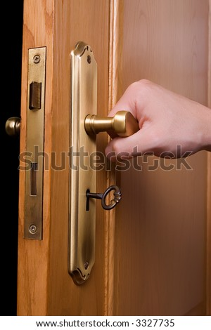 Hand on a handle wooden door to open or close it