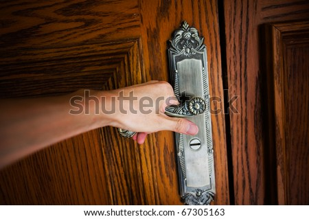 Hand on a handle wooden door to open or close it. - stock photo
