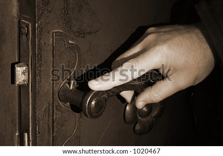 Hand on an antique door - opening - stock photo