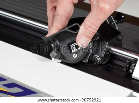 Hand on blade of mat cutter cutting into a white mat for framing a picture