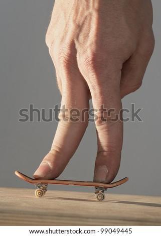 Hand on finger skateboard - stock photo