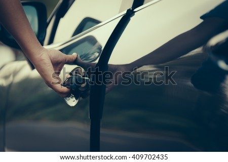 Hand on handle. Close-up of man hand opening a car door. vintage picture style process. - stock photo