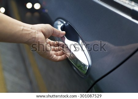 Hand on handle, man opening a car door on the street