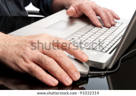 Hand on mouse and computer keyboard