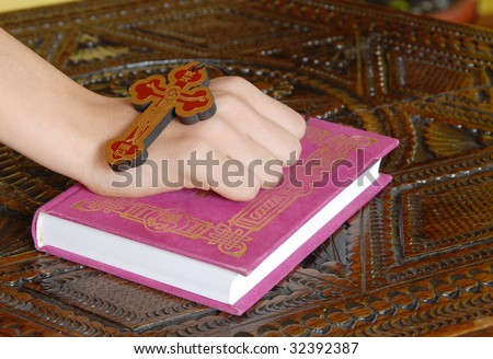 Hand on red Bible with wooden cross