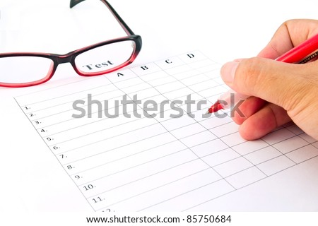 Hand on red pen choosing the test list and glasses on the examination