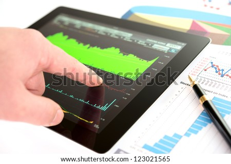 Hand on screen tablet pc with business information - stock photo
