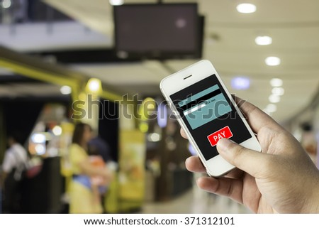 Hand on smartphone and click on pay button for mobile payment from credit card on the screen with blurred of people are walking in shopping center. - stock photo
