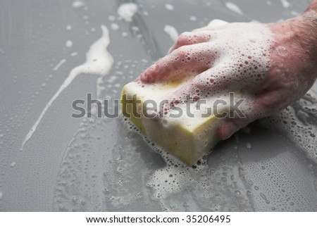 Hand on sponge washing car