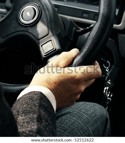 Hand on steering wheel - stock photo