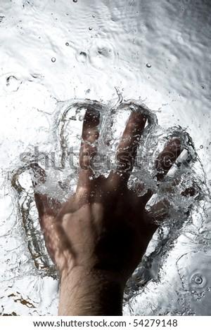 Hand on the Black water . Creative splashing dark water - stock photo