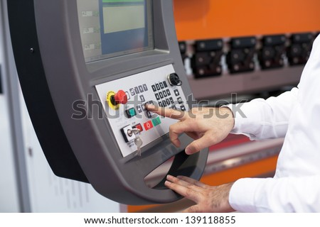 Hand on the control panel of a programmable machine - stock photo