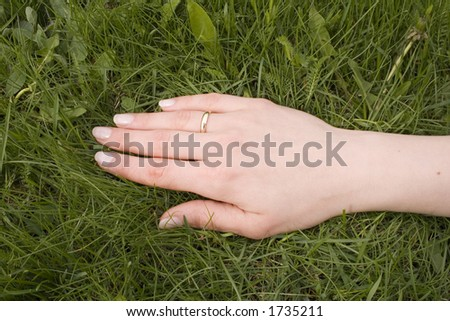 Hand on the grass with wedding ring - stock photo
