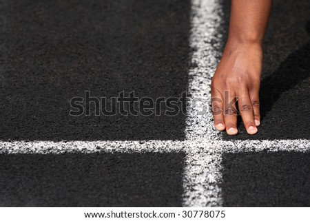 Hand on the starting line of a race (shallow depth of field) - stock photo