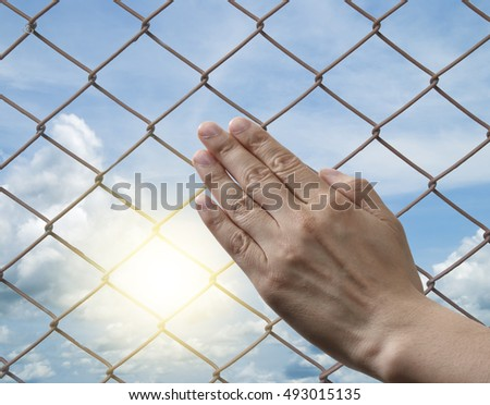 hand on wire fence pattern with cloud sky background