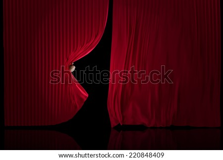 Hand opening a three dimensional realistic stage curtains on a black background. - stock photo