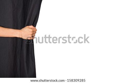 Hand opening black curtain. Isolated on white background. - stock photo