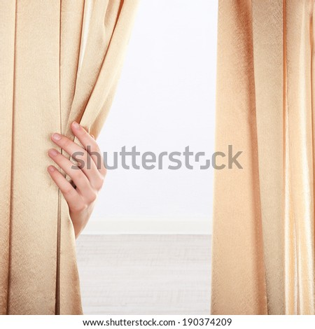 Hand opening curtain on wall background - stock photo