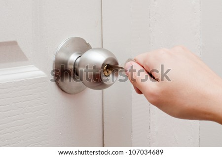 hand opening door by key - stock photo