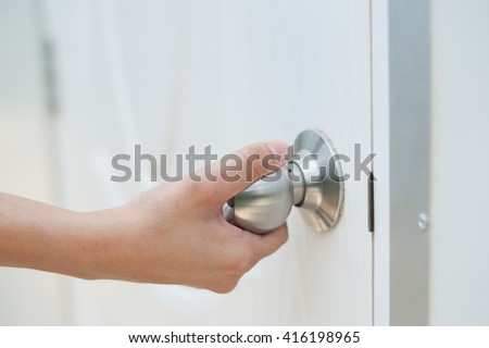 Hand opening door knob-white door - stock photo