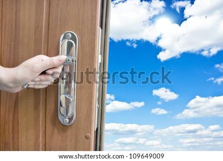 hand opening the door with sky - stock photo