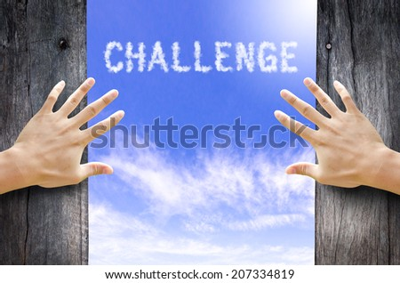 "Hand opening the wooden door and see ""Challenge"" text cloud in the Sky. - stock photo"