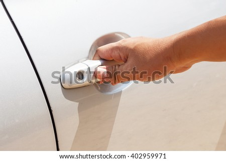 Hand opens door of gray metalic car close up