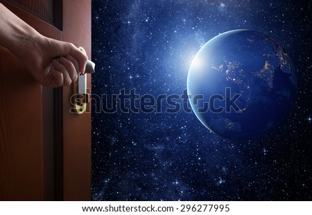 hand opens empty room door to Planet earth from the space. Some elements of this image furnished by NASA - stock photo