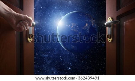 hand opens room door to galaxy - stock photo