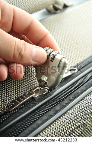 hand opens suitcase combination lock - stock photo