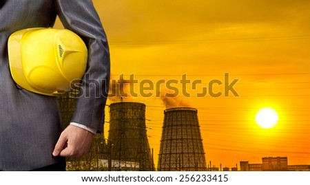 Hand or arm of engineer hold yellow plastic helmet for workers security over Central Electric Heat CHP in winter Empty space for inscription Yellow sunset sky with clouds - stock photo