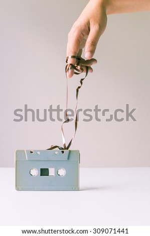 Hand over messy tape from retro cassette. - stock photo