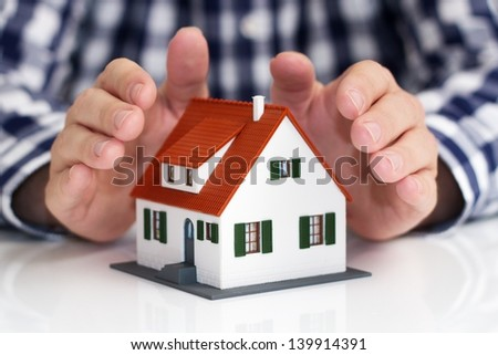 Hand over mini house with depth of field - stock photo