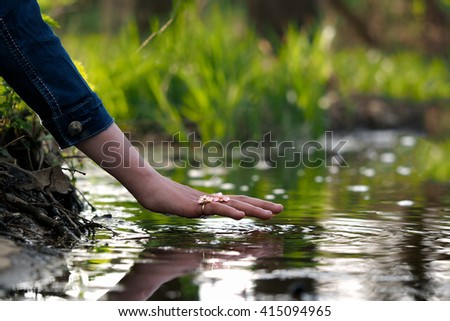 Hand over the water. Hand female, finger ring. Water is green, summer. Feng Shui - stock photo