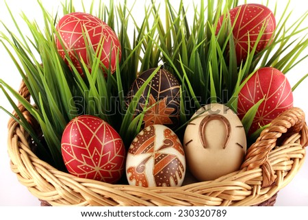 Hand-painted easter eggs in the wicker basket, white pattern - stock photo