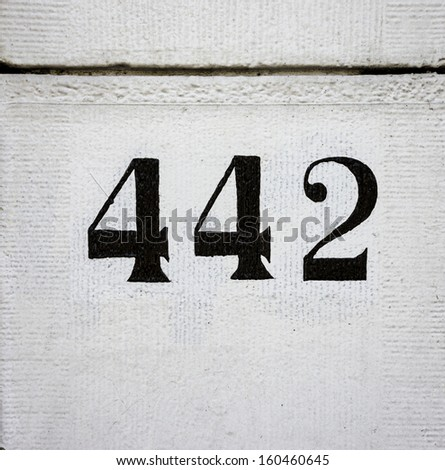 hand painted house number four hundred and forty two. Black lettering on white wall. - stock photo