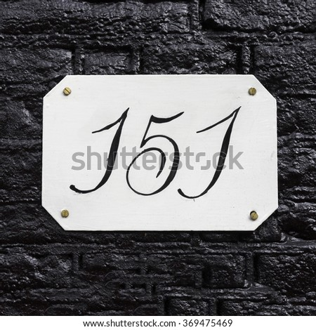 hand painted house number one hundred and fifty one. - stock photo