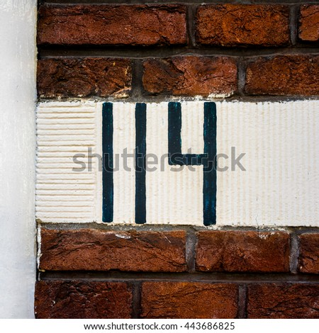 hand painted house number one hundred and fourteen - stock photo