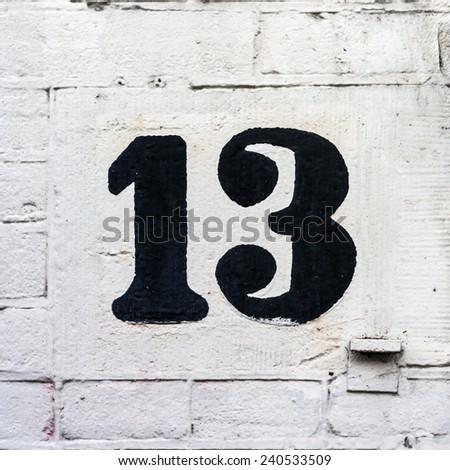 hand painted house number thirteen - stock photo