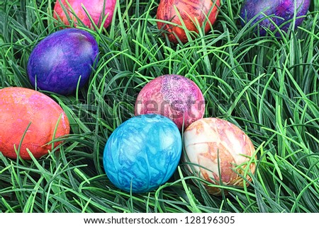Hand painted tie dyed Easter eggs in the grass. Extreme shallow DOF. - stock photo