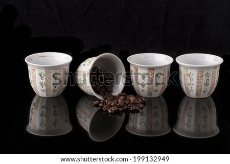Hand painted traditional arabic coffee cups on black background and coffee beans with reflection - stock photo