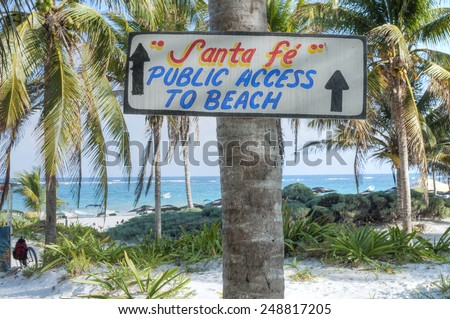 Hand-painted wooden sign on coconut palm directs visitors to beautiful public beach in Tulum on the the Mexican Riviera - stock photo